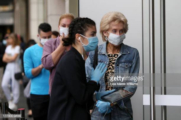 Staff member assists customers on the street prior to entering the Bondi Junction store on May 07, 2020 in Sydney, Australia. Apple stores across...