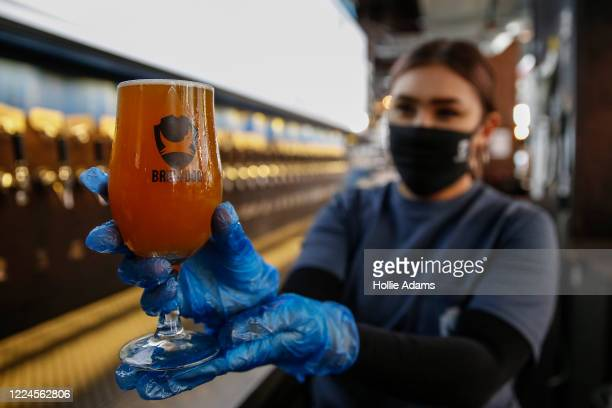 Staff member at BrewDog Tower Hill holds up a Pineapple Coconut Crumb beer as they prepare to reopen tomorrow with social distancing measures in...