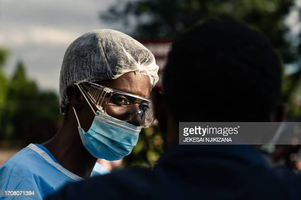 A staff member at the Parirenyatwa Hospital screens and gives hand sanitiser and hand wash to visitors entering the hospital as the country tries to...