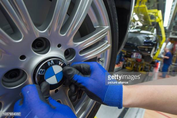 A staff member attaches the BMW logo to a wheel of a BMW car model at the assembly plant of car manufacturer BMW in Regensburg Germany 13 March 2015...