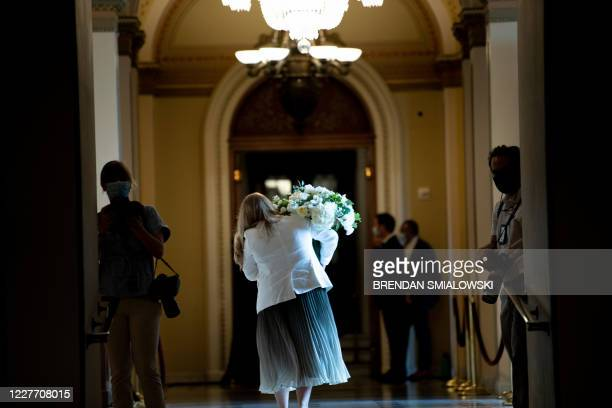 A staff member brings flowers to the House floor on Capitol Hill before a moment of silence for civil rights activist Rep John Lewis who died last...