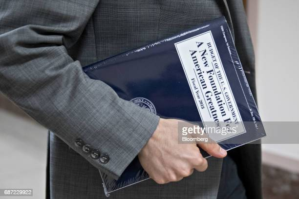A staff member carries a copy of US President Donald Trump's fiscal 2018 budget proposal on Capitol Hill in Washington DC US on Tuesday May 23 2017...