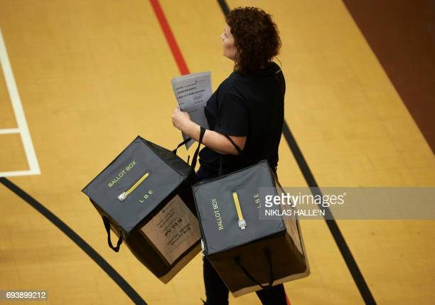 A staff member carries ballot boxes at a counting centre in Islington London on June 8 after the polls closed in Britain's general election Prime...