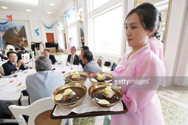A staff member carries cold noodles during a lunch for North Korean leader Kim Jong Un and South Korean President Moon Jaein at the Okryugwan...