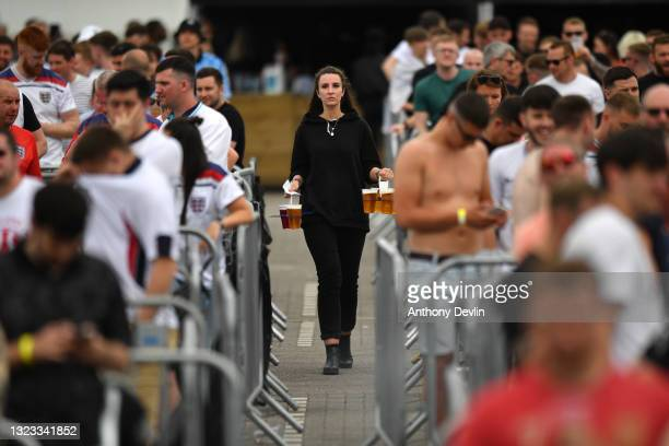 Staff member carries drinks to tables at the 4TheFans fan zone at Event City on June 13, 2021 in Manchester, England. Fanzones and pubs are hosting...