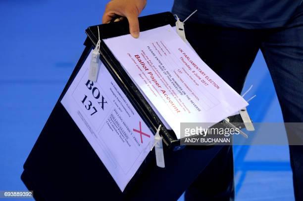 A staff member carries one of the first ballot boxes as they arrive at the main Glasgow counting centre in Emirates Arena in Glasgow Scotland on June...
