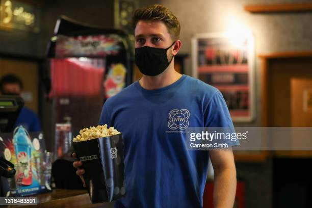 Staff member carries popcorn in The Plaza cinema on May 17, 2021 in Truro, England. England implements the third step in its road map out of...