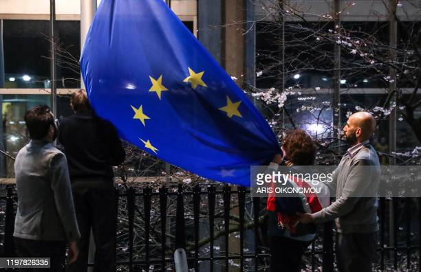A staff member carries the United Kingdom's flag after taking it down from the European Parliament building in Brussels on Brexit Day January 31 2020...