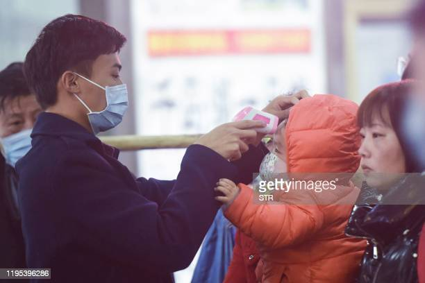 A staff member checks body temperature of a child after a train from Wuhan arrived at Hangzhou Railway Station in Hangzhou China's eastern Zhejiang...