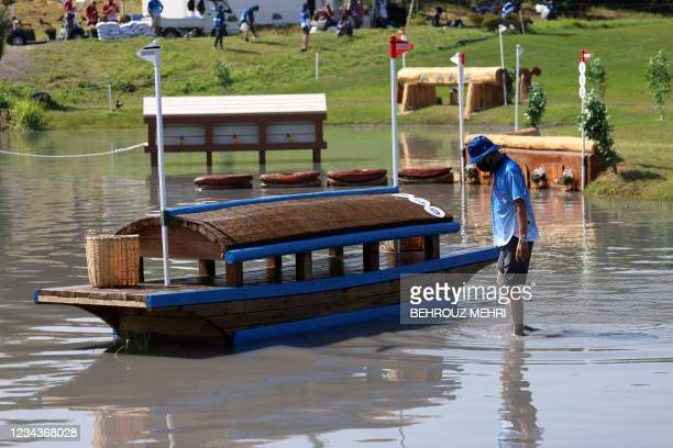 Staff member checks on an obstacle during the equestrian's eventing team and individual cross country during the Tokyo 2020 Olympic Games at the Sea...