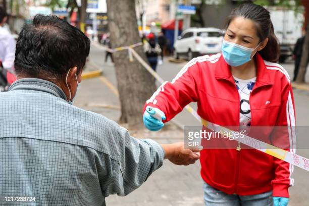 A staff member checks the body temperature for a man to be tested for the COVID19 coronavirus on a street in Mudanjiang Chinas northeastern...