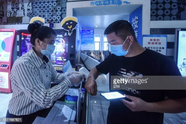 Staff member checks the body temperature of a man before he enters a cinema in Hangzhou in China's eastern Zhejiang province on July 20 on the first...