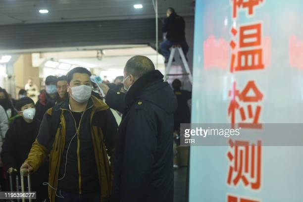 Staff member checks the body temperature of a passenger after a train from Wuhan arrived at Hangzhou Railway Station in Hangzhou, China's eastern...