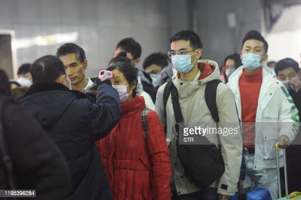 A staff member checks the body temperature of a passenger after a train from Wuhan arrived at Hangzhou Railway Station in Hangzhou China's eastern...