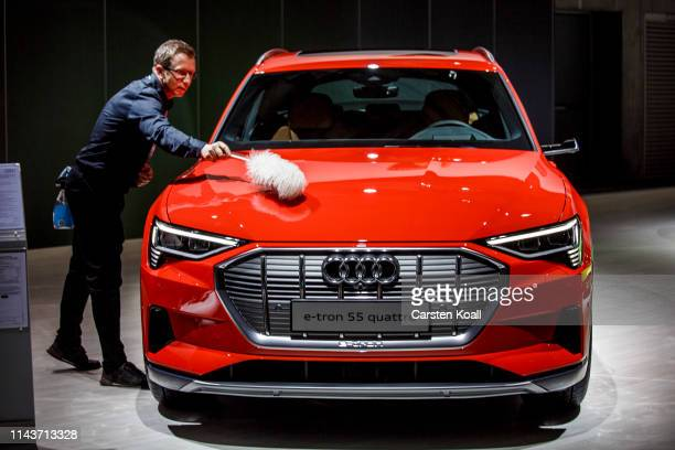 A staff member cleans an Audi etron 55 Quattro during the Volkswagen AG company's annual shareholders' meeting on May 14 2019 in Berlin Germany...