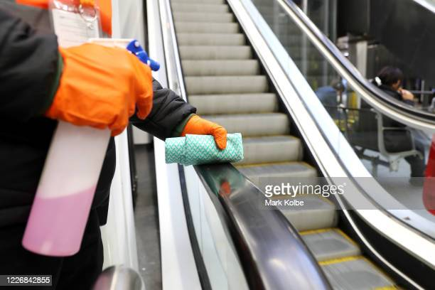Staff member cleans the handrail of an escalator at Wynyard station on May 25, 2020 in Sydney, Australia. Additional security and marshalling staff...
