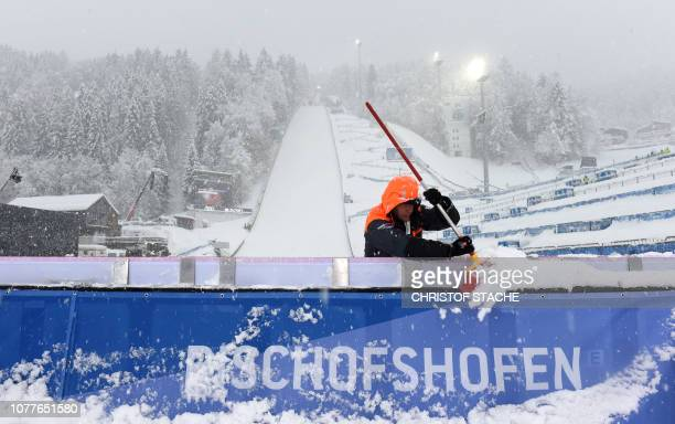 A staff member clears snow at the ski stadium ahead of the trainings and qualifiers rounds of the fourth stage of the FourHills Ski Jumping...