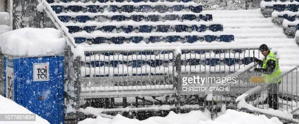 A staff member clears the stairs from the snow covering the stands ahead of the trainings and qualifiers rounds of the fourth stage of the FourHills...