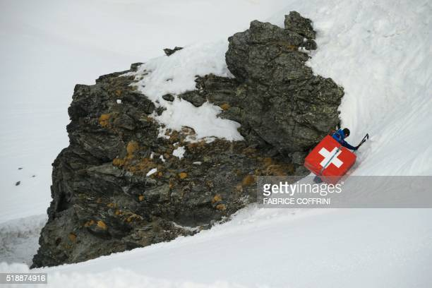 A staff member climbs a safety mattress bearing the Swiss flag on a ski slope of the Swiss Alps resort of Verbier on April 3 2016 / AFP / FABRICE...