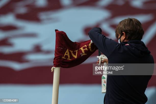 Staff member disinfects a corner flag prior to the English Premier League football match between Aston Villa and Sheffield United at Villa Park in...