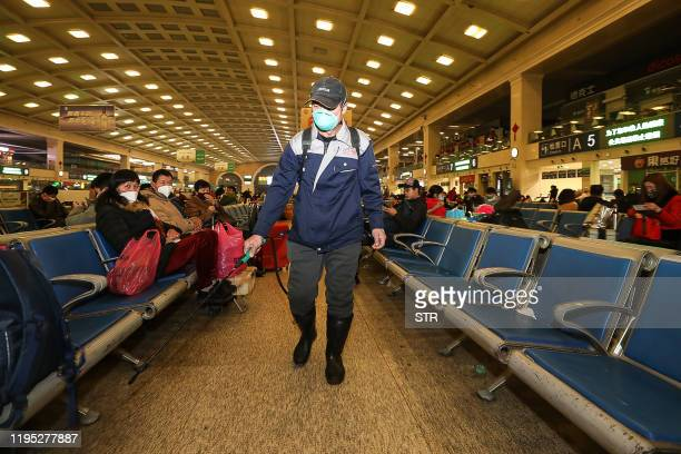 TOPSHOT A staff member disinfects at the Hankou Railway Station in Wuhan in China's central Hubei province early on January 22 2020 The Chinese city...
