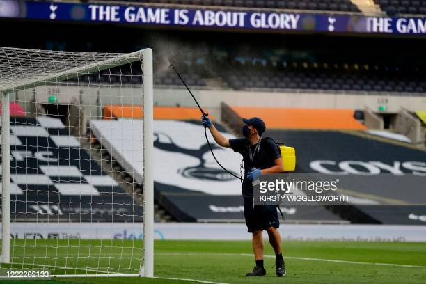 Staff member disinfects the goal during the English Premier League football match between Tottenham Hotspur and West Ham United at Tottenham Hotspur...