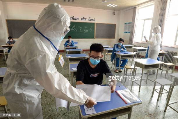Staff member distributes papers to a student at an isolation examination room set for students at risk of infection by the COVID-19 coronavirus,...