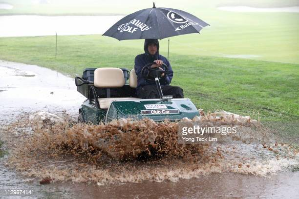 Staff member drives along the course as play is suspended due to rain during the first round of the Genesis Open at Riviera Country Club on February...