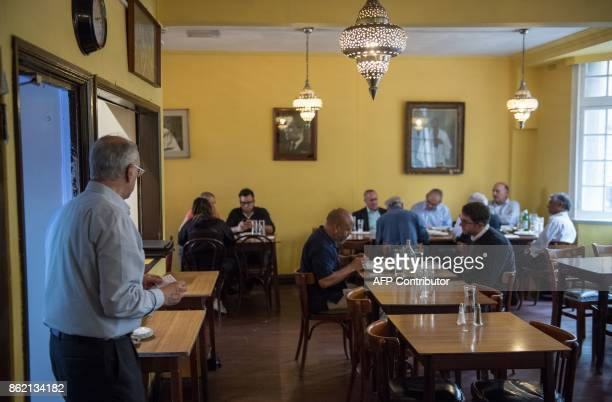 A staff member exits the kitchen as people eat lunch inside the India Club restaurant in London on October 16 2017 Plans to renovate a historic and...