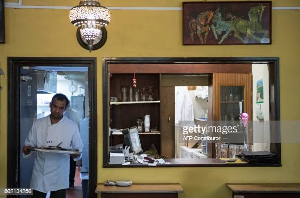 A staff member exits the kitchen inside the India Club restaurant in London on October 16 2017 Plans to renovate a historic and beloved Indian...