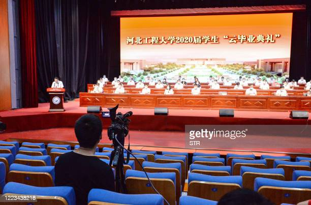 Staff member films a live-streaming of a graduation ceremony at Hebei University of Engineering in Handan in China's northern Hebei province on June...