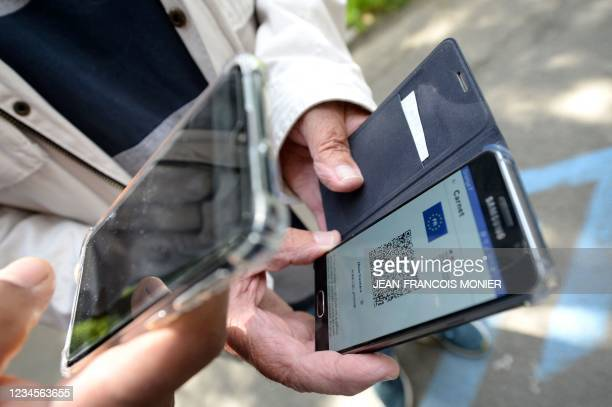 Staff member flashes a QR code of a suporter's Covid-19 health pass before the start of the French L1 football match between Stade Rennais Football...
