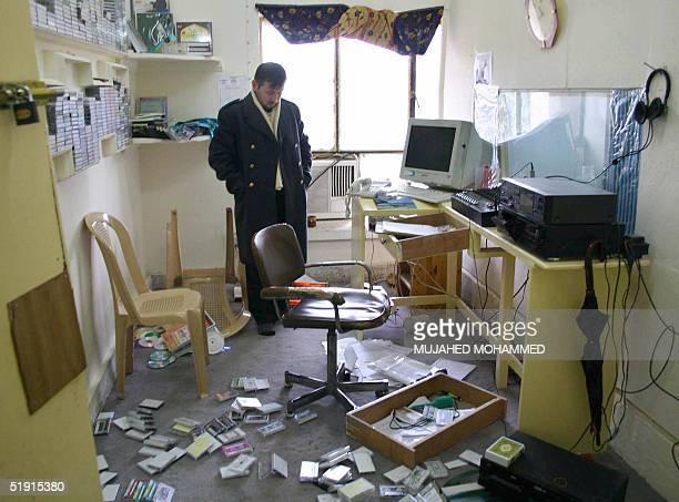 A staff member from the Iraqi Islamic party Iraq's main Sunni Muslim party looks at the ransacked offices of their headquarters in the northern city...