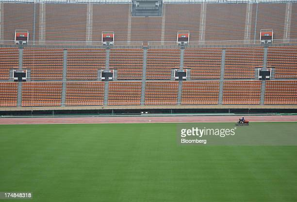 A staff member grooms the pitch of the existing National Olympic Stadium built for the 1964 Olympic games which will be demolished to make way for a...