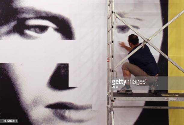 A staff member hangs a poster of late fado singer Amalia Rodrigues on October 1 2009 at the Centro Cultural de Belem in Lisbon The Museum Berardo in...