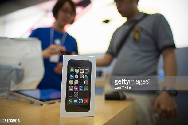 A staff member helps a customer with the new iPhone 5s and iPhone 5C models inside Apple's store in Causeway Bay district on September 20 2013 in...