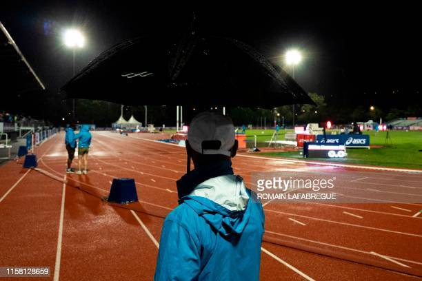 A staff member holds an umbrella as rain falls during the France Athletics Championships 2019 at the HenriLux stadium in SaintEtienne central eastern...