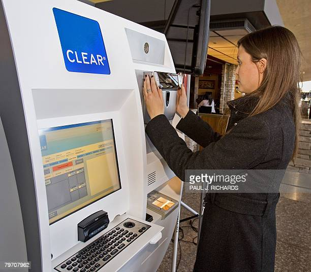 CLEAR staff member Katy Darnaby stands and get a retinal scan as she demonstrates part of the process to get the CLEAR airport biometric fast pass...