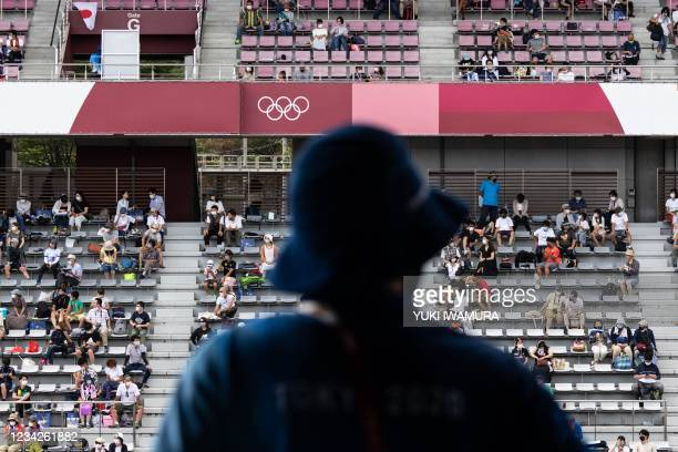 Staff member look at spectators watching the men's cycling road individual time trial during the Tokyo 2020 Olympic Games at the Fuji International...