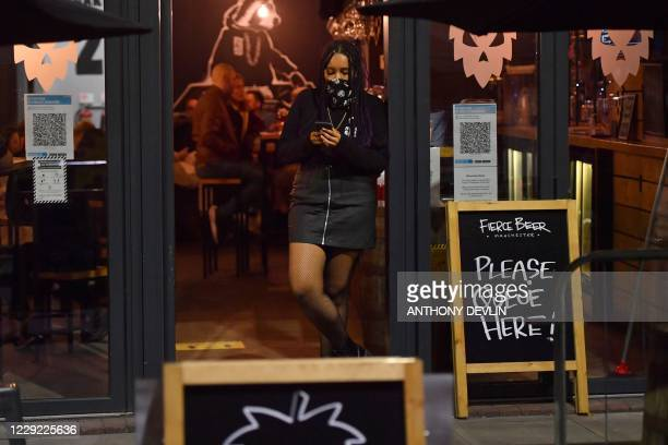 A staff member looks at a mobile phone in the doorway of a bar on Dale Street in Manchester city centre northwest England ahead of new coronavirus...