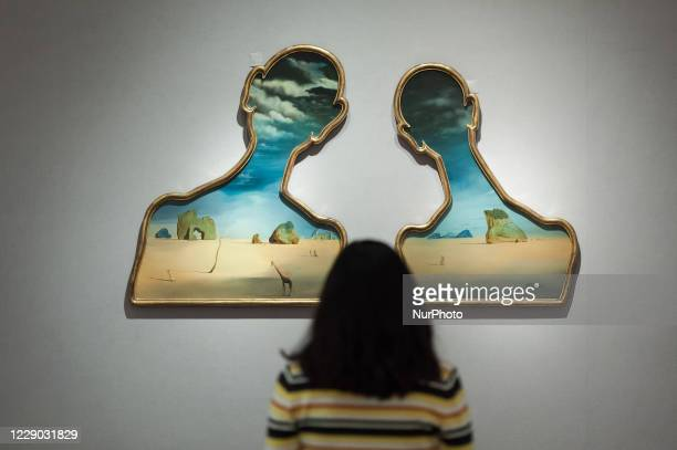 Staff member looks at Couple aux tetes pleines de nuages by Salvador Dali during a photo call for Bonhams' Impressionist and Modern Art Sale, on...