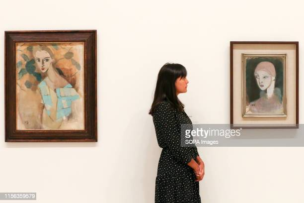 A staff member looks onto the Helene Schjerfbeck's painting Girl from the Islands 1929 at the Royal Academy of Arts during the preview of her first...