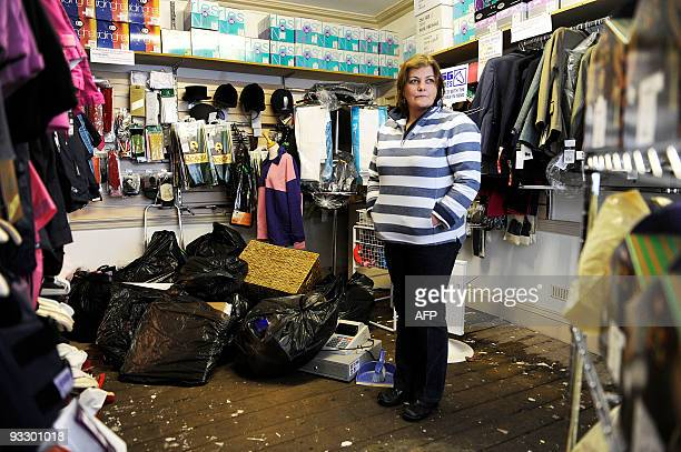 A staff member of a store in Dumfries southwest Scotland stands amongst spoiled goods on November 22 2009 after some 314 millimetres of rain fell in...