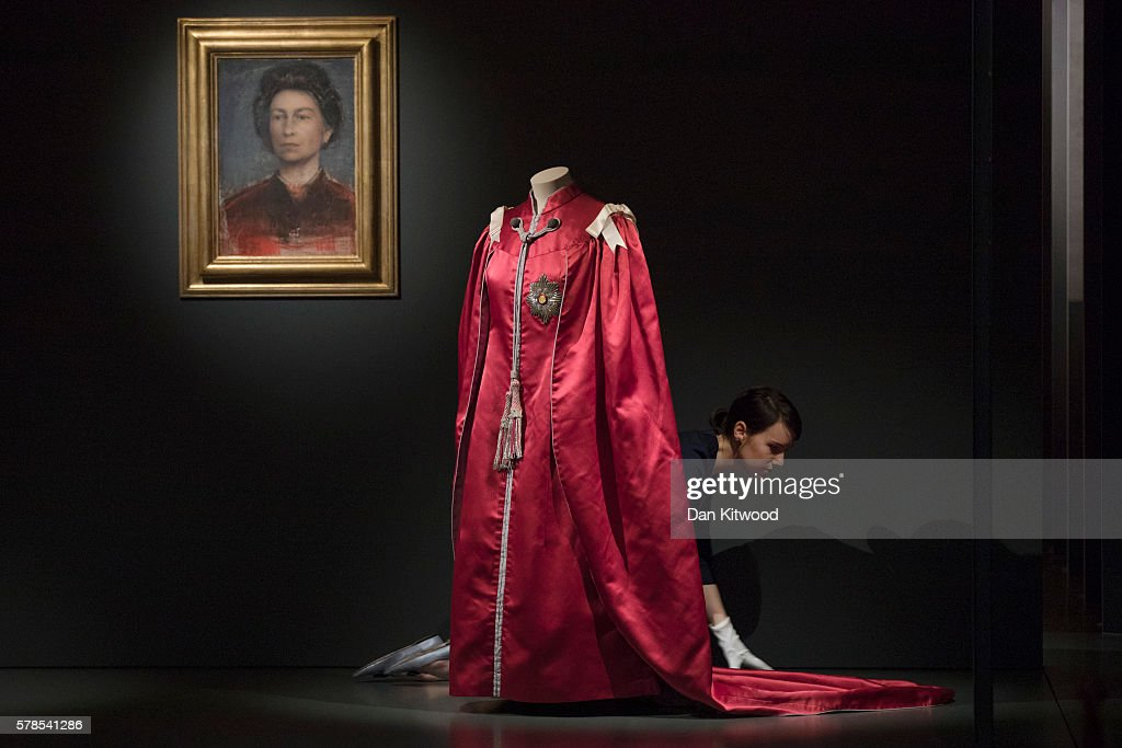 A staff member of Buckingham Palace adjusts the train of a Mantle of the British Empire, by Ede and Ravenscroft and made by Marion Faole in 1952 during a photocall at Buckingham Palace on July 21, 2016 in London, England. The piece makes up part of a forthcoming exhibit 'Fashioning a Reign: 90 Years of Style from The Queen's Wardrobe' to coincide with the Summer Opening of Buckingham Palace. The exhibit includes outfits worn by the Queen from State events to family celebrations and runs until October 2, 2016.