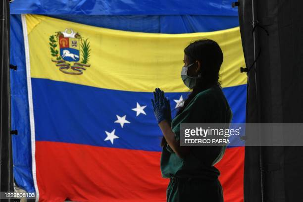 Staff member of Doctors Without Borders prepares herself waits for patients to be tested for COVId-19 in front of a Venezuelan flag at the Perez de...