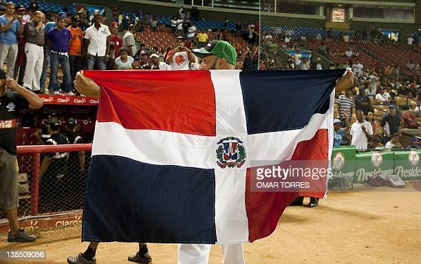A staff member of Dominican Leones del Escogido displays his national flag at the end of the Caribbean Series baseball game against Puerto Rican...