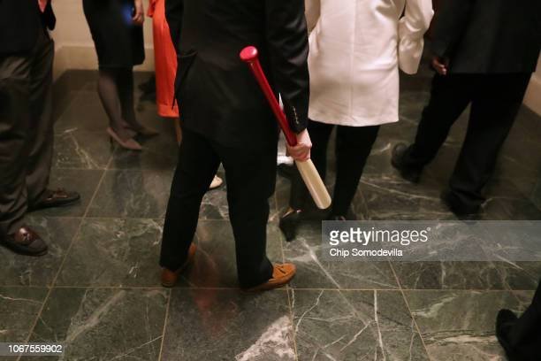 A staff member of House Majority Whip Steve Scalise carries a baseball bat into a caucus meeting in the Longworth House Office Building on Capitol...