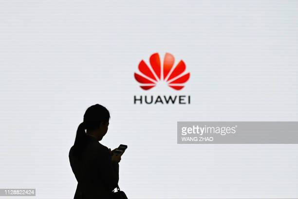 A staff member of Huawei uses her mobile phone at the Huawei Digital Transformation Showcase in Shenzhen China's Guangdong province on March 6 2019...