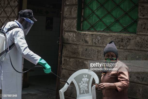 A staff member of Kenya's Ministry of Health sprays disinfectant at a chair in front of public toilet to curb the spread of the COVID19 coronavirus...