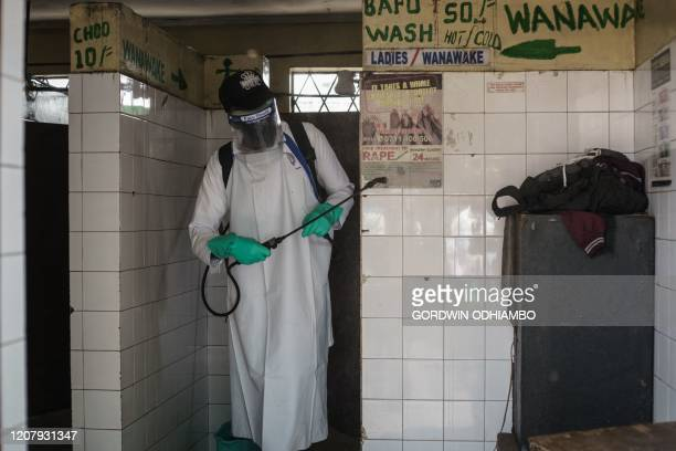 A staff member of Kenya's Ministry of Health sprays disinfectant in a public toilet to curb the spread of the COVID19 coronavirus at the Gikomba...